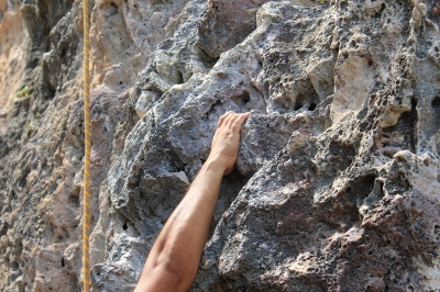 hand hanging on rock face