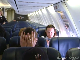 Man on flight covering face, looking scared