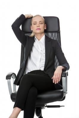 Woman sitting on office chair with eyes closed